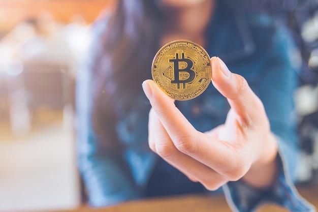 A mão de uma mulher segurando uma moeda, bitcoin.