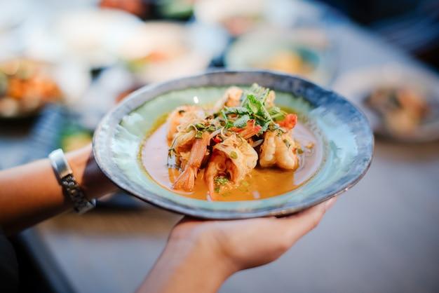 A mão de uma mulher segurando uma salada de camarão