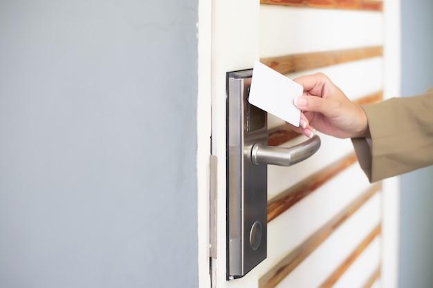 A mão de uma mulher segurava um cartão-chave para destrancar a porta