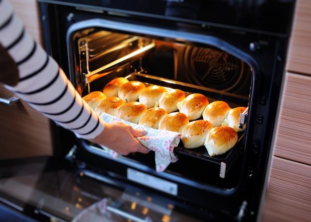 A mão de uma mulher tira do forno deliciosos bolos quentes com uma crosta dourada