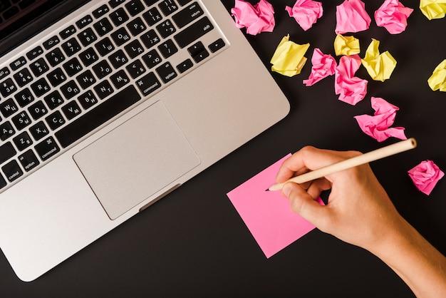 A mão de uma pessoa a escrever com lápis na nota adesiva sobre fundo preto