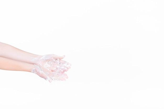 A mão de uma pessoa em espuma de sabão sobre fundo branco