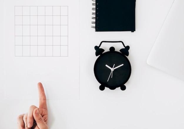 A mão de uma pessoa que aponta o dedo no papel com calendário vazio; despertador e diário na mesa branca