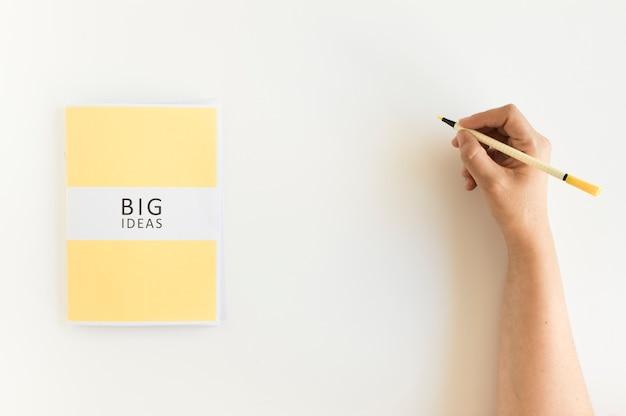 A mão de uma pessoa que escreve no fundo com o diário grande das ideias