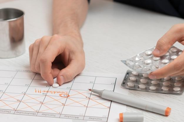 A mão de uma pessoa segurando comprimidos, fazendo o plano de programação no calendário, cuidados de saúde
