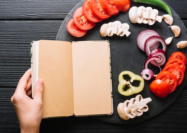 A mão de uma pessoa segurando diário perto de legumes fatiados em pano de fundo preto de madeira