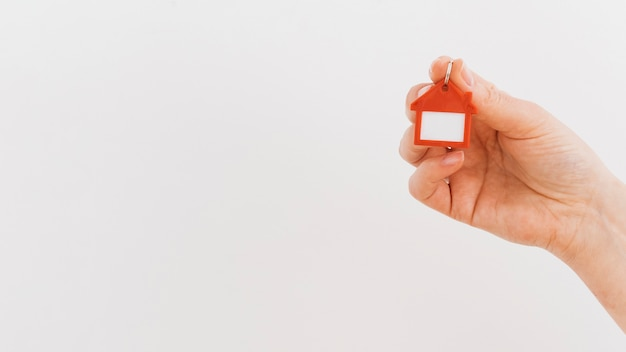 A mão de uma pessoa segurando o chaveiro de casa em pano de fundo branco
