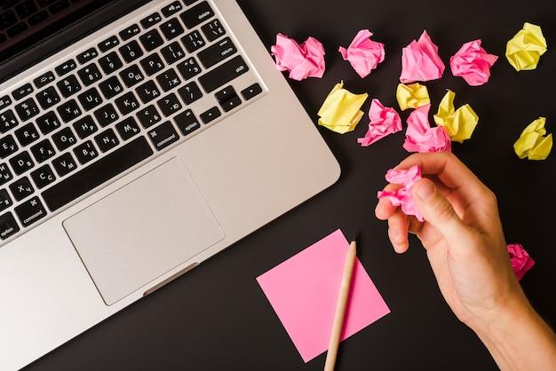 A mão de uma pessoa segurando papel amassado com laptop; caneta e papel adesivo em fundo preto
