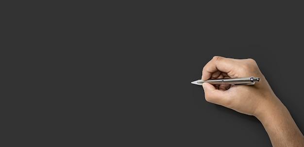 A mão de uma pessoa segurando uma caneta e prestes a escrever, isolada em um fundo cinza escuro e traçado de recorte.