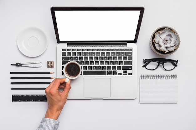 A mão de uma pessoa segurando xícara de café preto sobre o laptop na mesa de escritório