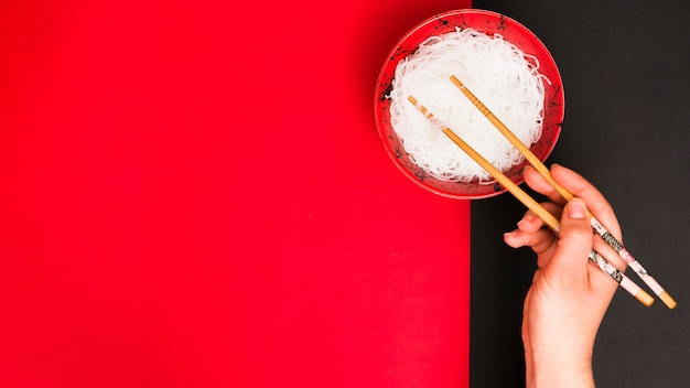A mão de uma pessoa usa pauzinhos para pegar macarrão cozido no vapor saboroso na tigela sobre duas mesa