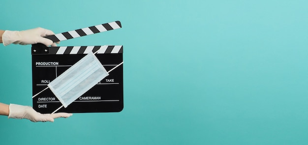 A mão deve usar luvas médicas brancas e segurar uma claquete preta ou uma tela de cinema com máscara facial. é usado em filmes, produção de filmes e indústria cinematográfica em fundo azul e verde.