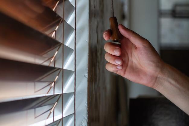 A mão direita do homem segura uma das cordas de controle das venezianas de madeira da janela.