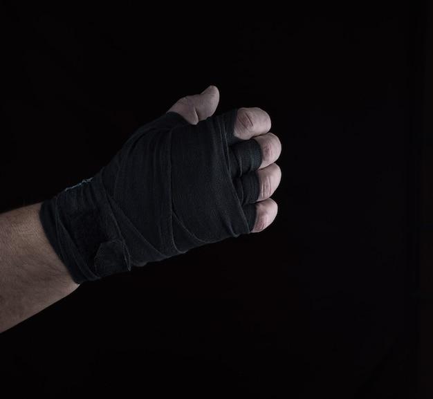 A mão direita masculina é envolvida em uma atadura preta de matéria têxtil dos esportes