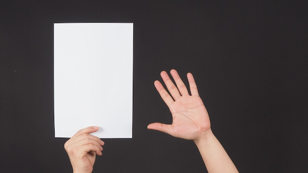 A mão direita masculina está segurando um papel a4 em fundo preto.