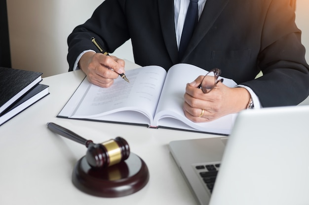 A mão do advogado escreve o documento em tribunal (justiça, lei) com bloco de som