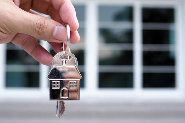 A mão do banqueiro segura a chave da casa. conceito de hipoteca de casa e terra