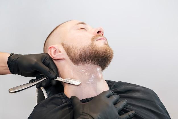 A mão do barbeiro com uma navalha raspa a barba na garganta do paciente.