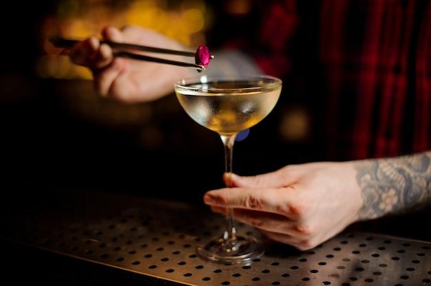 A mão do barman decorando o coquetel elegante com um pequeno botão de rosa rosa no balcão do bar