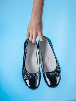 A mão do bebê segura elegantes sapatos de couro sobre fundo azul. sapatos femininos de couro elegantes e modernos.