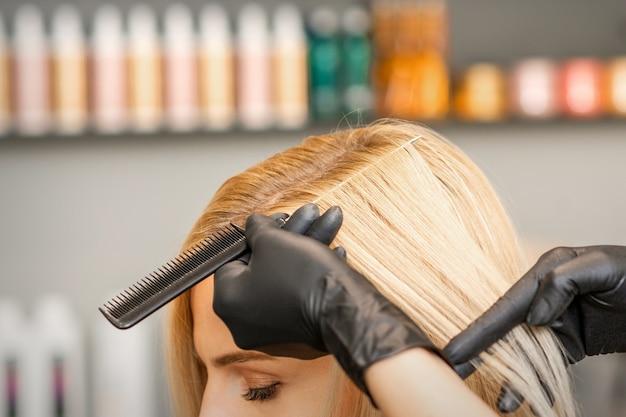A mão do cabeleireiro penteia o cabelo feminino antes de tingir em um salão de beleza
