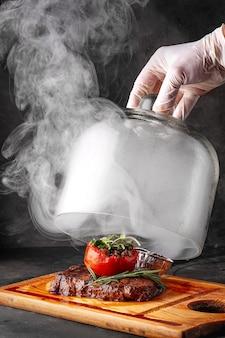 A mão do chef levanta a cúpula sobre o bife com vegetais e fumaça