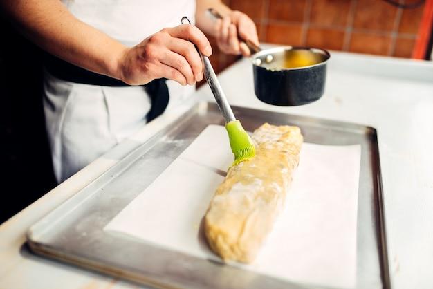 A mão do chef lubrifica strudel com ovo e manteiga