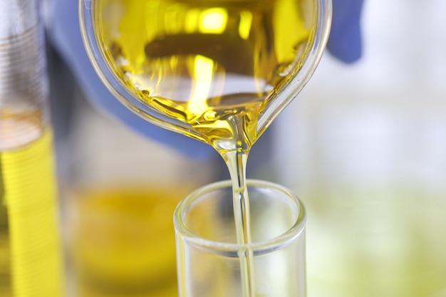 A mão do cientista em uma luva de borracha derrama um líquido amarelo em um tubo de ensaio de vidro em um laboratório químico