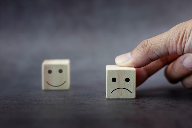 A mão do cliente do close up escolhe o ícone de rosto triste e o ícone de rosto triste desfocado no cubo de madeira