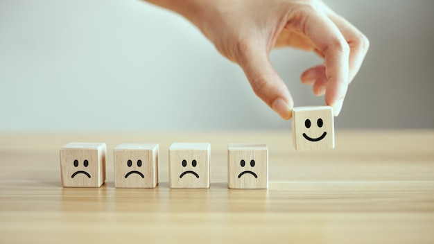 A mão do cliente do close up escolhe o ícone do rosto sorridente no cubo de madeira
