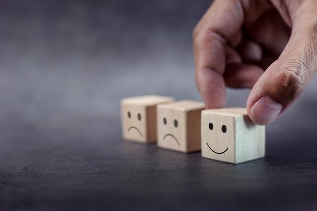 A mão do cliente escolhe o rosto sorridente e o rosto triste desfocado no cubo de madeira