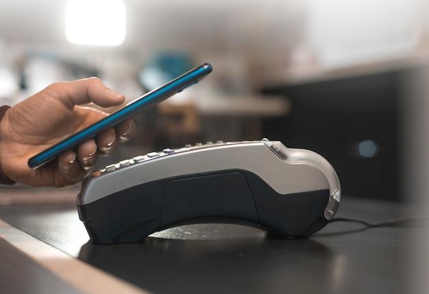 A mão do cliente paga com o smartphone na loja usando a tecnologia nfc. celular pagando a conta com menos tecnologia.