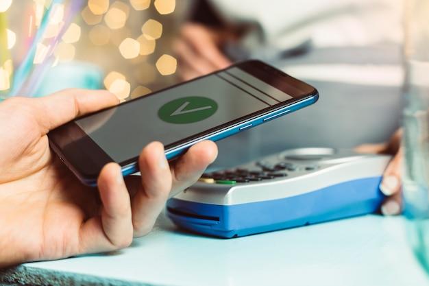 A mão do cliente paga com o smartphone na loja usando a tecnologia nfc