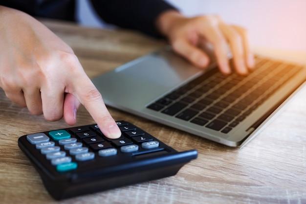 A mão do close up da mulher de negócio que trabalha com calculadora e portátil para analisa o relatório no escritório.