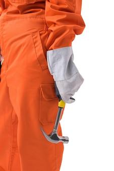 A mão do close up de um trabalhador da mulher no macacão do mecânico está mantendo o martelo isolado no fundo branco