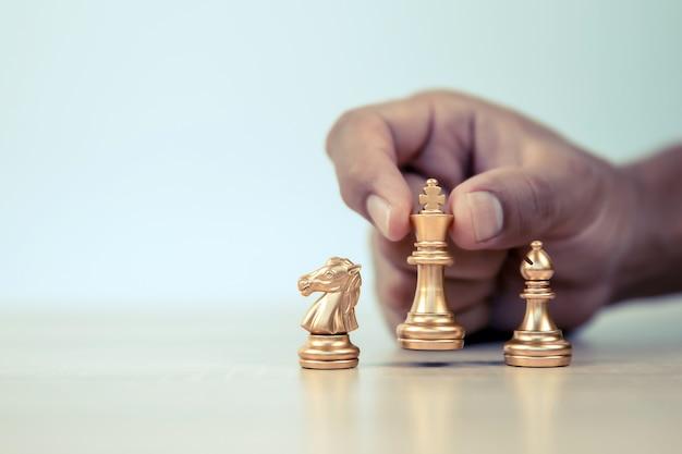 A mão do close-up escolhe a peça de xadrez do rei.