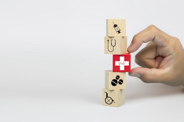 A mão do close-up escolhe blocos de brinquedo de madeira de um cubo com um ícone do ritmo cardíaco da cruz vermelha empilhado.