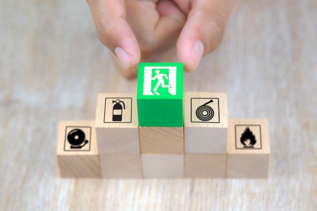 A mão do close-up escolhe blocos de brinquedo de madeira empilhados na pirâmide com ícone da saída de emergência.