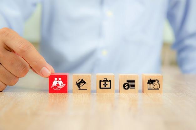 A mão do close-up escolhe blocos de brinquedo de madeira vermelhos com ícone da família.