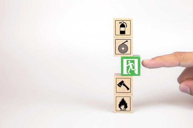 A mão do close-up escolhe blocos de um brinquedo de madeira com ícone da saída de emergência para a proteção de segurança contra incêndios, conceitos.