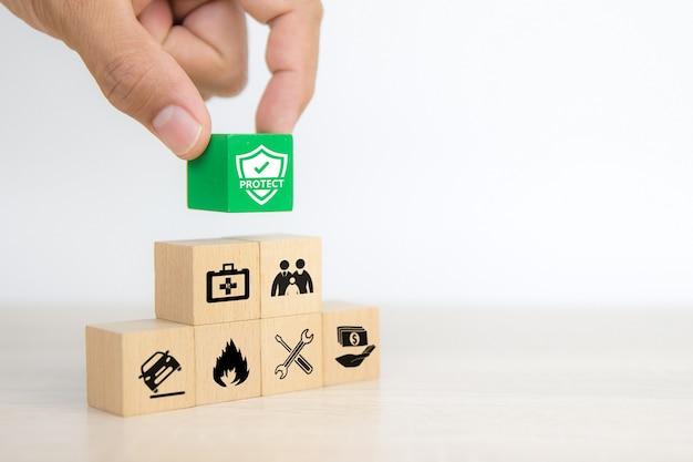 A mão do close-up escolhe o bloco de madeira com o ícone de prevenção de fogo.