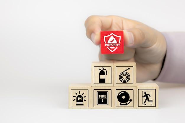 A mão do close-up escolhe o ícone de prevenção de incêndio em blocos de brinquedo de madeira do cubo empilhados com o ícone de prevenção de incêndio.