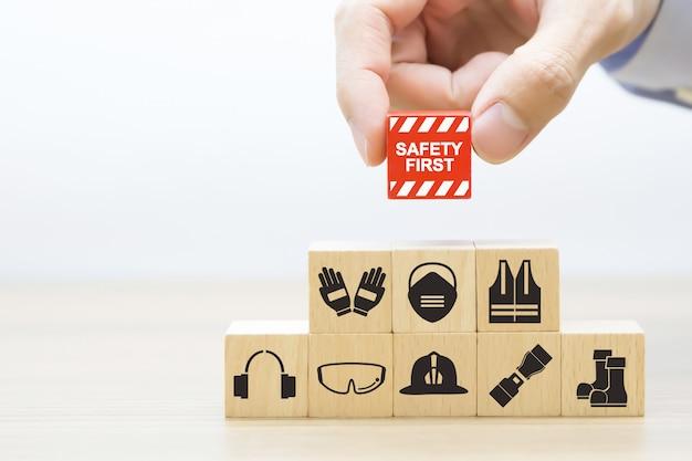 A mão do close-up escolhe os blocos de madeira empilhados com primeiros ícones da segurança.