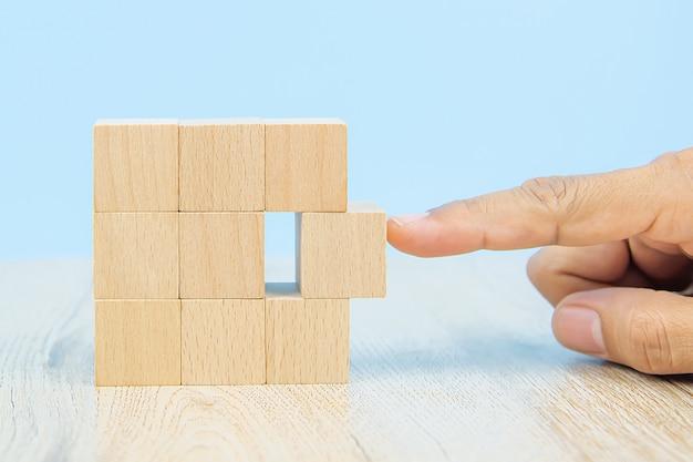 A mão do close-up escolhe um brinquedo de madeira do bloco da forma do cubo empilhado sem gráficos para o conceito e a atividade de projeto de negócio para habilidades da prática da fundação da criança.