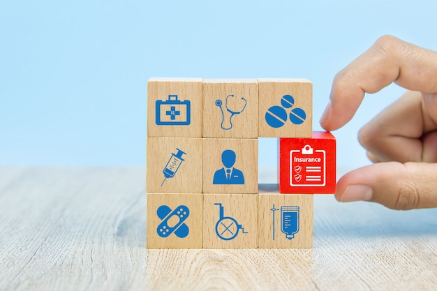 A mão do close-up escolhe um brinquedo de madeira vermelho bloqueia com ícone do seguro para o seguro de vida familiar de segurança