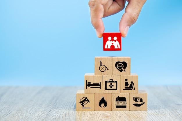 A mão do close-up escolhe um cubo vermelho os blocos de madeira do brinquedo empilhados na forma da pirâmide com ícone da família.
