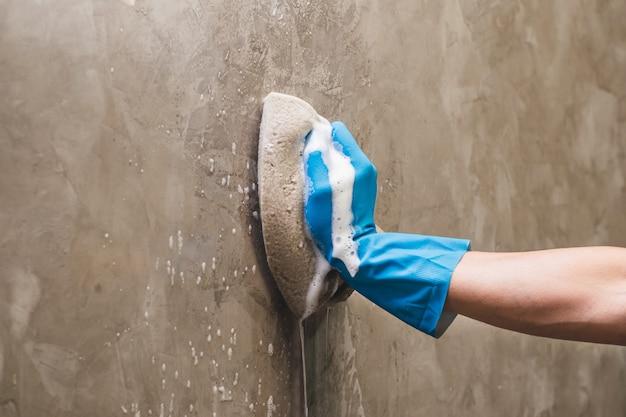 A mão do close up que veste luvas de borracha azuis está usando uma limpeza da esponja na parede de concreto.