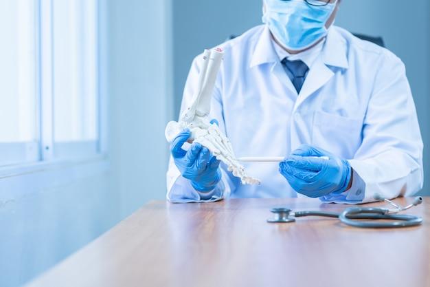 A mão do close-up veste o doutor médico das luvas em luvas médicas prende o boneof artificial o pé no hospital.