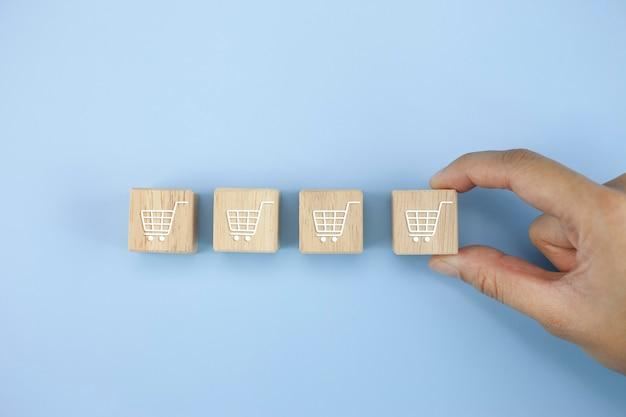 A mão do close up vira o cubo com o símbolo do ícone do carrinho de compras
