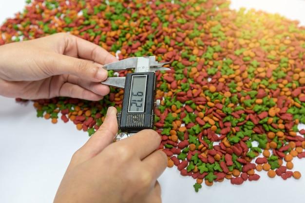 A mão do controle de qualidade está usando o tamanho de croquete medido no compasso de calibre vernier para controlar a qualidade.